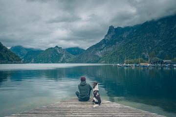 Mężczyzna z psem siedzą na pomoście nad jeziorem w górach w pochmurny dzień