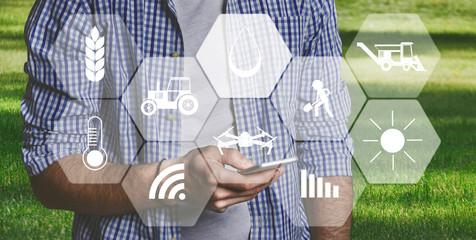 Man farmer with digital tablet in field using apps