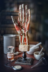 Vintage layout of a man's hand, old medical utensils on the background of a medical office. Old medical, education and science background.