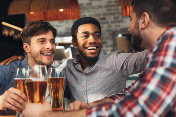 Sharing News. Diverse Friends Drinking Beer In Bar