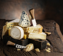 Wall Mural - Assortment of different cheese types on wooden background. Cheese background.