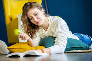 Blonde woman reading book at home and laying on the floor next to yellow armchair