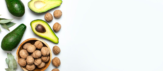 Wall Mural - Ripe fresh avocado, walnuts in wooden bowl, eucalyptus twigs on white background top view Flat lay copy space. Fruits Healthy food concept, diet, healthy lifestyle.