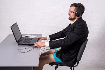 Man dressed in a suit and shorts siting with a laptop. Fototapete