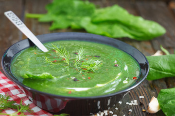 Green spring pureed spinach soup in a bowl decorated with dill and cream. Healthy food, wooden table.