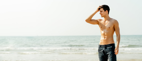 Panoramic banner image of portrait of sexy muscular man with closes eyes and smiling at the beach. Beautiful Happy Guy with sexy body sunbathing and Healthy Skin Sun Tan Tanning.. wide crop.