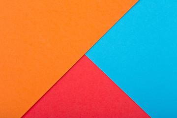 Colored paper texture. Geometric figure. Red color, orange color and blue color.
