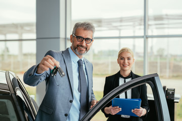 businessman holding car keys of his new car in car showroom