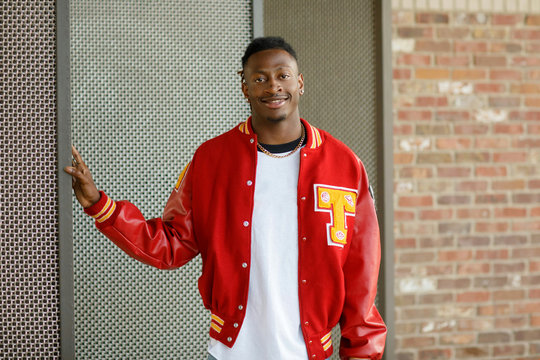 Male High School Senior in Red Letterman Jacket for Sports standing in an Urban Area