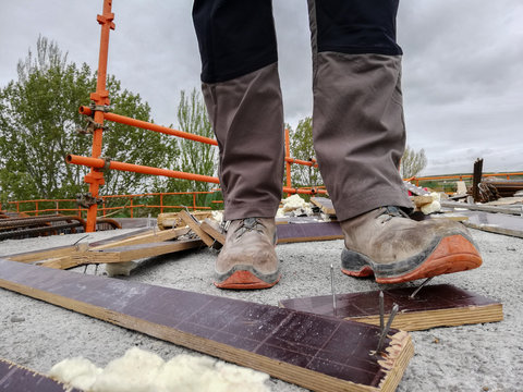 A construction worker has an acciden while walks through a site with debris and stepping on a nail