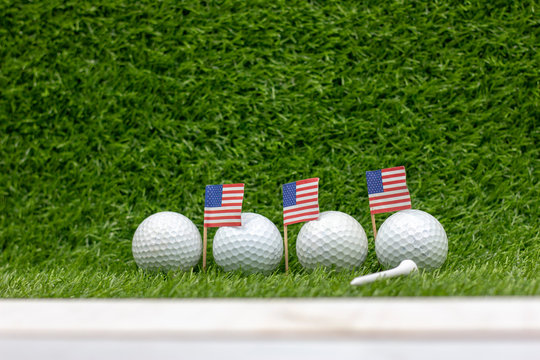 Golf ball with flag of American flag on green grass 4th July