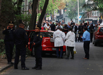 Members of the forensic team work at a crime scene where according to local media one man was killed and other was injured when gunmen opened fire at a vehicle along the street at La Condesa neighbourhood in Mexico City