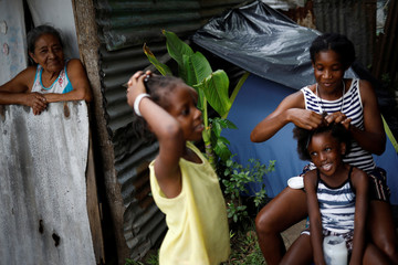 A Mexican woman looks as a Haitian migrant combs a girl in Tapachula