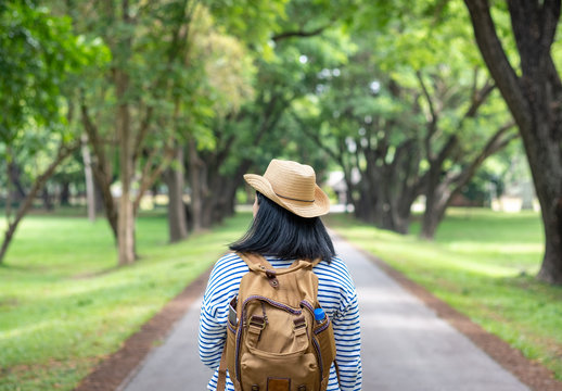 Happy young traveler woman backpacker travel in green natural forest ,greenery fresh air,Freedom wanderlust concept,Alone solo journey
