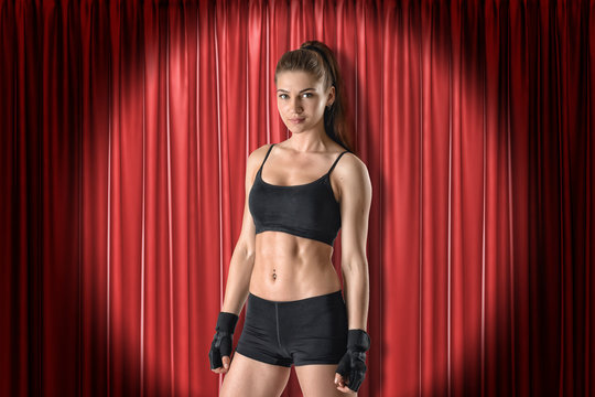 Front crop view of young woman in black crop top, shorts and fingerless gloves standing in spotlight at red stage curtain and looking at camera.