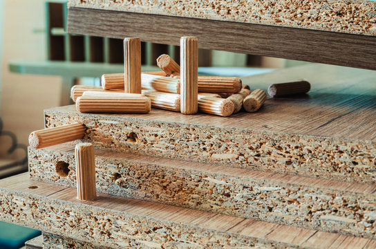 Furniture fittings, wooden dowels, fastener connection on chipboard workpieces, close-up