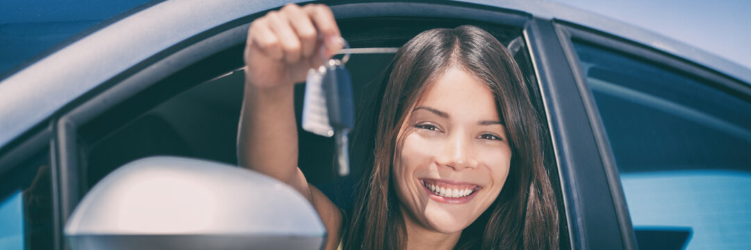 New Car driver young Asian woman driving automatic drive smiling showing new car keys banner panorama.