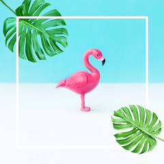 Flamingo bird model with monstera leaf on color background.