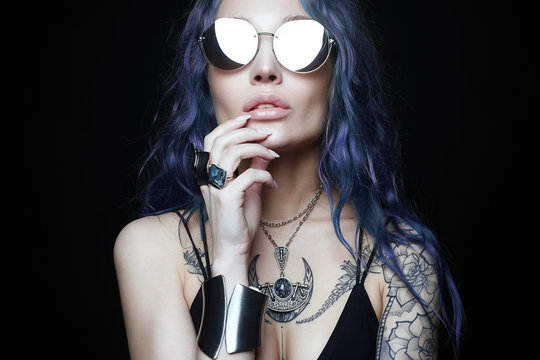 Beautiful young woman with blue hair tattoo. freak style