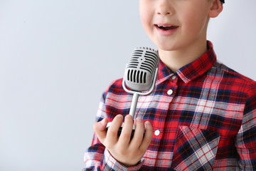 Cute little boy with microphone singing against light background
