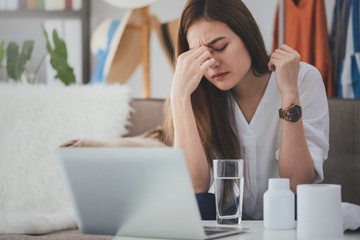 Asian beautiful women stressful and headache after working with a laptop for a long time.Hand holding the face After taking a headache medication.Office syndrome concept.