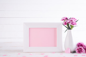 White picture frame with lovely pink carnation flower in vase on white wooden table.