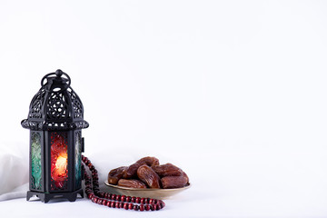Ramadan food and drinks concept. Ramadan Lantern with arabian lamp, wood rosary, tea, dates fruit and lighting on a wooden table on white background.