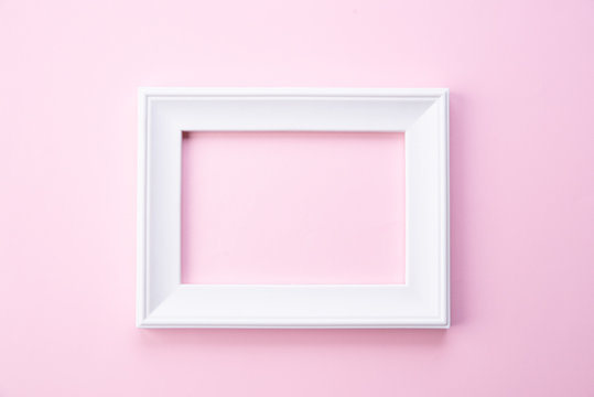 Happy Mothers day concept. Top view of white picture frame on pink pastel background. Flat lay.
