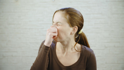 Woman close her nose because it smell bad