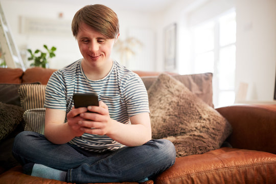Young Downs Syndrome Man Sitting On Sofa Using Mobile Phone At Home