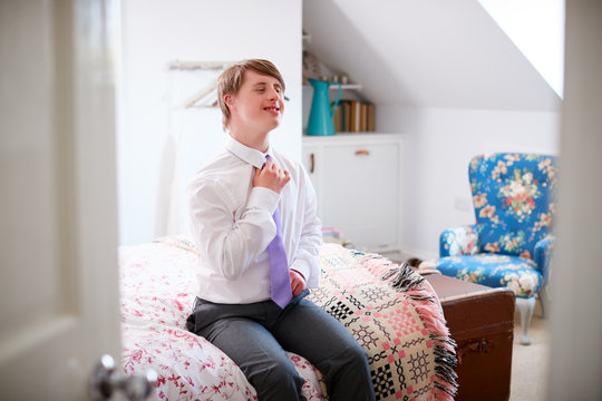 Young Downs Syndrome Man Sitting On Bed Getting Dressed For Work