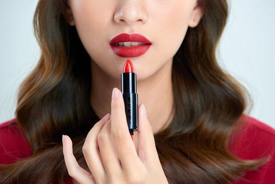 Detail of a beautiful woman applying lipstick