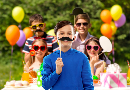 party props, photo booth and childhood concept - smiling boy in blue hoodie with black moustaches over group of friends on birthday in summer park background