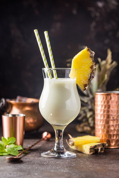 Homemade frozen Pina Colada cocktail with rum, coconut milk and pineapple garnish over black background
