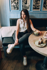 A pensive girl with a cap of coffee in her hands sitting in a cafe and looks into the distance