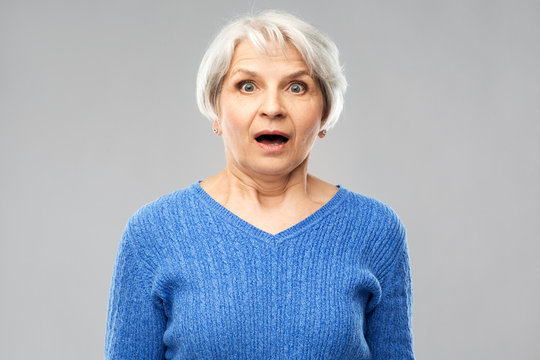 emotion, expression and old people concept - portrait of shocked senior woman in blue sweater with open mouth by hands over grey background