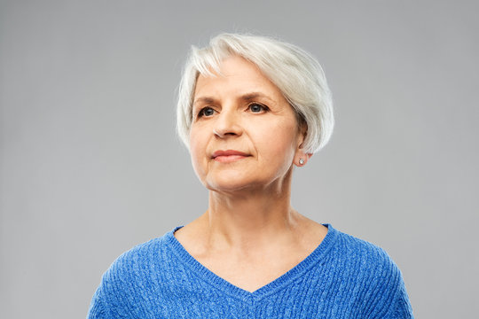 old people concept - portrait of senior woman in blue sweater over grey background