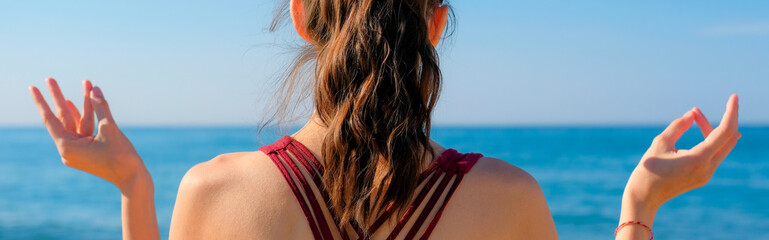 Woman wearing yoga top with cross strips back. Girl meditating on a pebble beach by the sea at sunny day with clear blue sky.