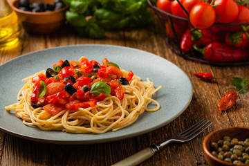 Italian spaghetti alla Pultanesca with tomatoes and olives. Served without meat and cheese.