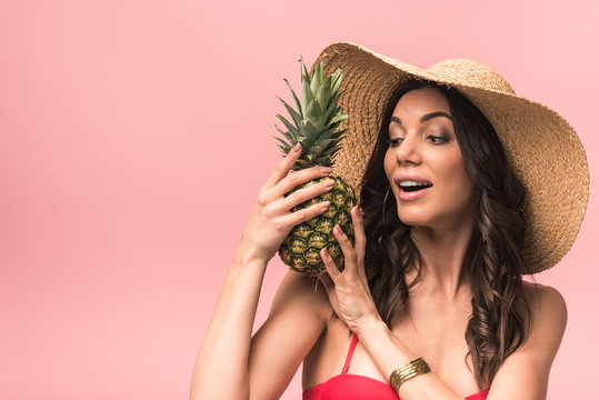 amazed girl in straw hat and bikini holding pinapple isolated on pink