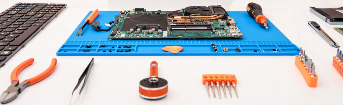 The repairman works in technical support, is engaged in the restoration and cleaning of the laptop.