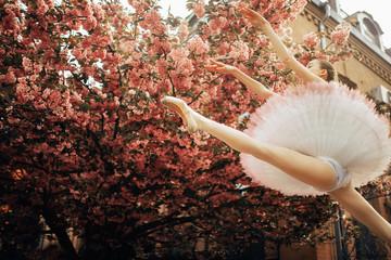 Ballerina jumping in twine pose against the background of flowering sakura trees.