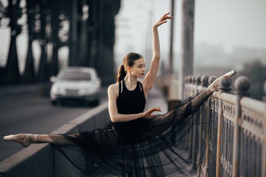 Ballerina sitting in twine pose on the bridge against the background of car and road.