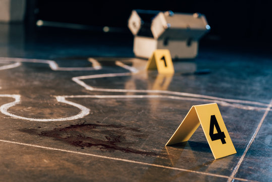 chalk outline, blood stain, investigation kit and evidence markers at crime scene