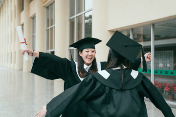 c1f1b22eaaa Two young student girls dressed in black graduation gown smiling holding  diplomas hugging. woman open