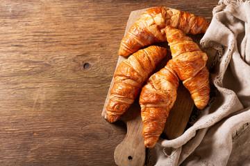fresh croissants on wooden board