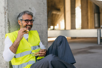construction worker in protective wear having lunch break on site