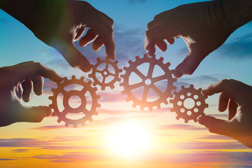 hands of businessmen assemble a puzzle from gears against the sky in the sunset. Business concept idea, partnership, cooperation, strategy, teamwork. innovation.
