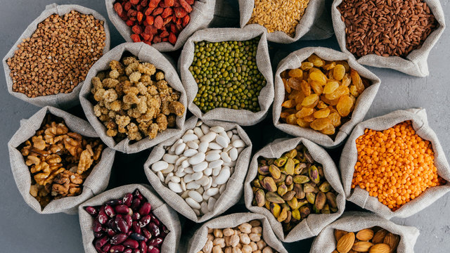 Various grains and dried fruit in hessian bags on market stall. Top view. Set of organic healthy products. Healthy eating concept