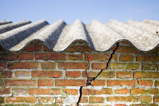 Asbestos roof above a cracked brick wall
